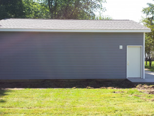 Side view of newly constructed outdoor garages with updated roofing in Clio, MI