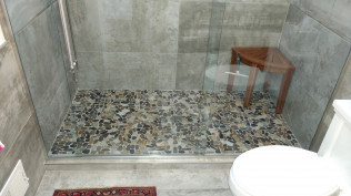 A brand new shower with stone tile in a remodeled bathroom in Clio, MI