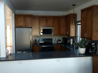 Wood cabinets and new counter tops in remodeled kitchen in Clio, MI